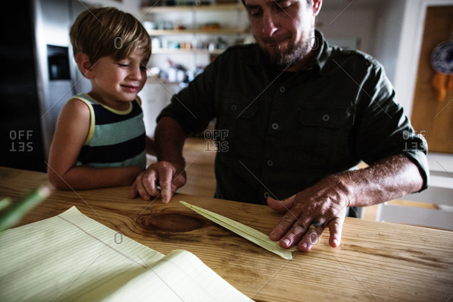 Boy watches his father fold a paper airplane