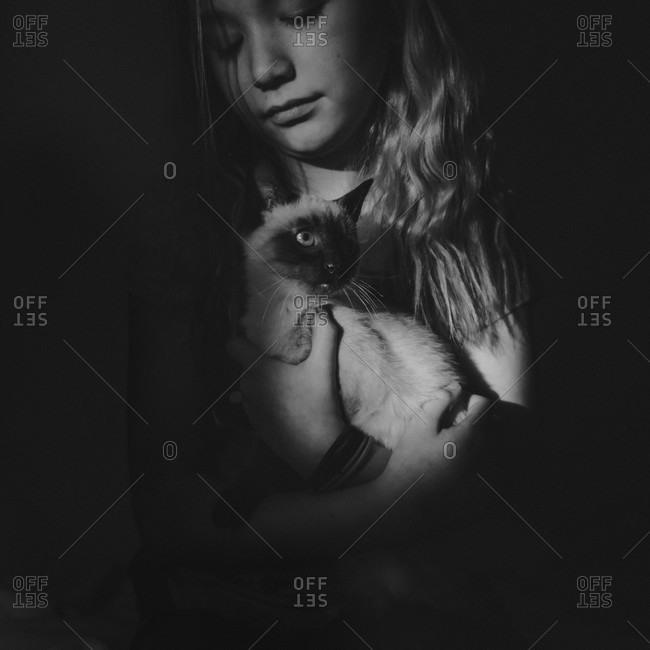 Girl holding her Siamese kitten