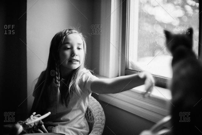 Girl shooing a cat away