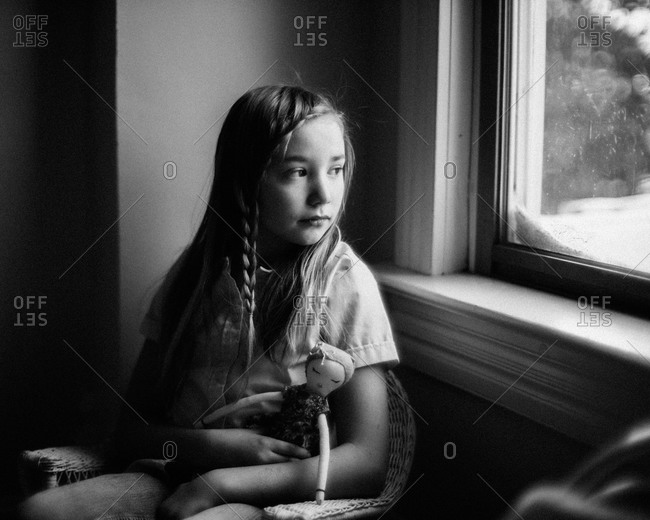 Girl sitting by a window with her doll