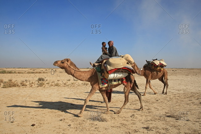 Lahore, Pakistan - January 29, 2000: A man and child riding a camel in the desert