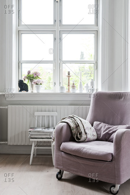 A purple armchair next to a window