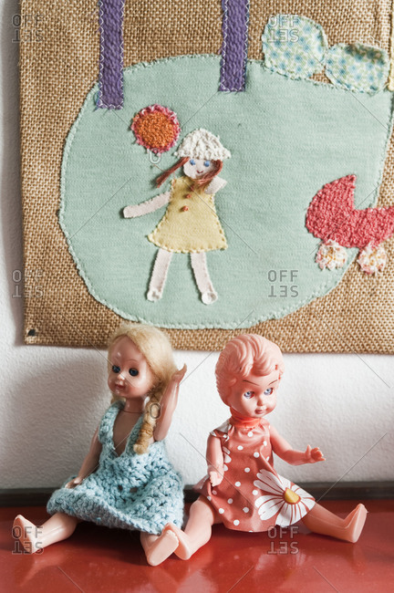Plastic dolls beneath an embroidered picture