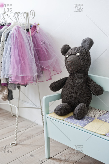 A little girl's wardrobe and a stuffed teddy bear