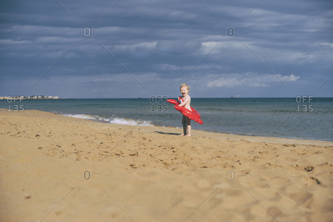 Girl with red crab swim toy at the beach