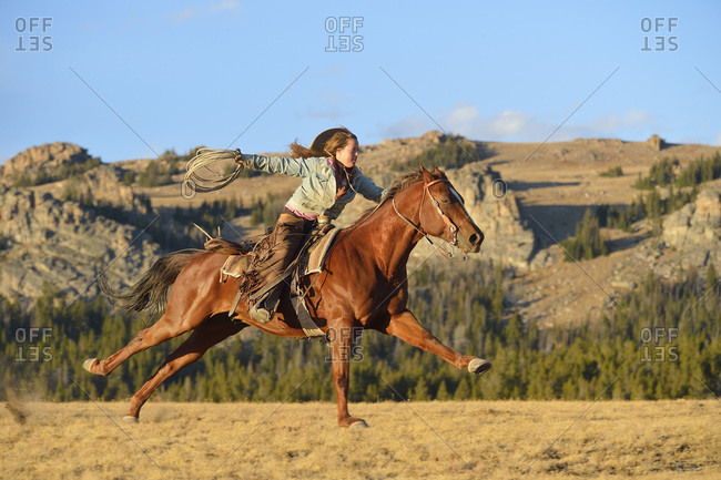 Riding cowgirl holding lasso - Offset