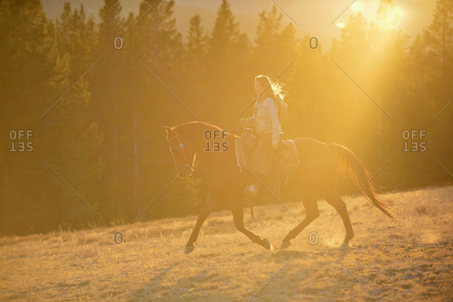 Cowgirl riding in evening light