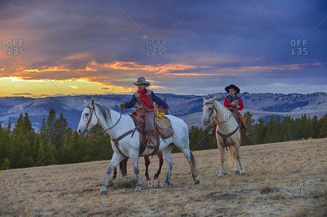 Two young cowboys riding in wilderness at sunset