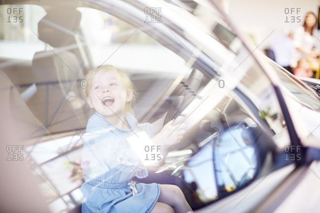 Happy girl at car dealer inside car