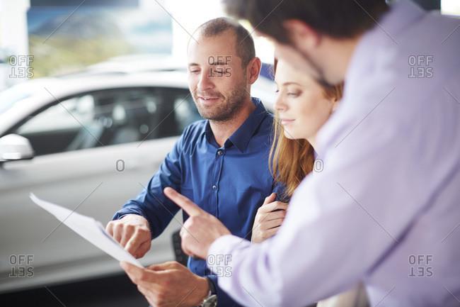 Couple at car dealer buying new car