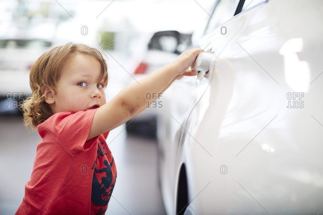 Boy at car dealer examining car