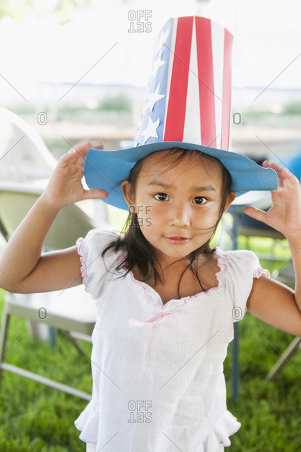 Portrait of young girl outdoors wearing a patriotic paper hat