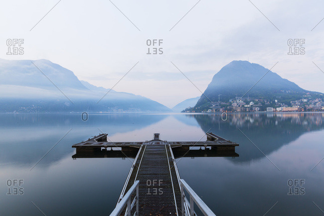 Landing stage in front of a reflection of monte San Salvatore in Lago Lugano in Spring