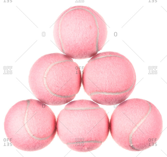 Six pink tennis balls stacked in a pyramid