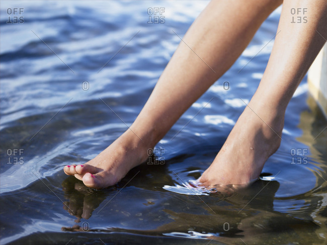 A woman dips her feet in a lake
