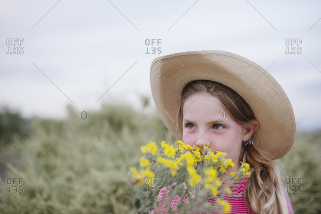 Portrait of girl in desert with flowers and cowboy hate