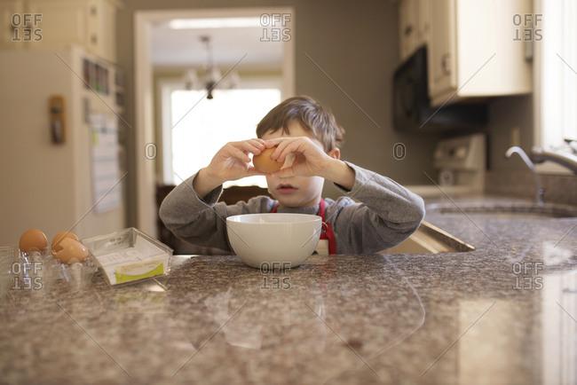 Child cracking egg into bowl