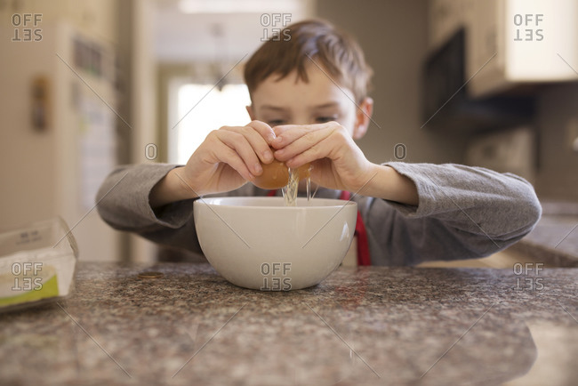 Child breaking an egg into a bowl