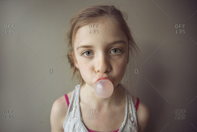 Portrait of a girl blowing a bubble with gum