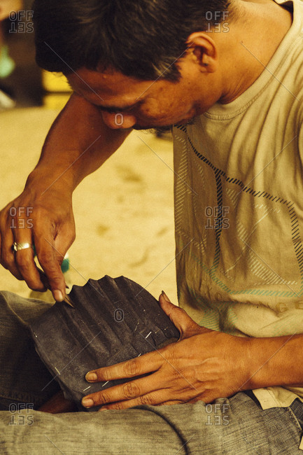 Bali, Indonesia - October 1, 2010: A man molds leather with a wooden tool  at an Indonesian clothing manufacturing factory