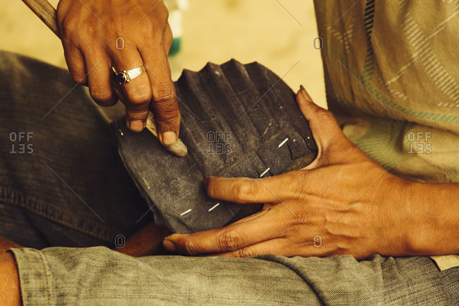 A man molds leather with a wooden tool  at an Indonesian clothing manufacturing factory