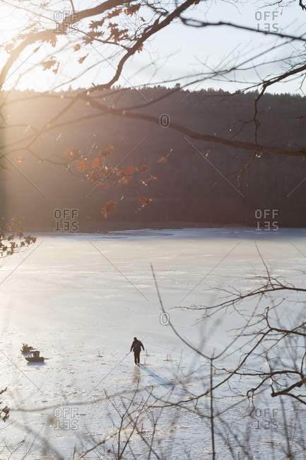 A man going ice fishing on a frozen lake