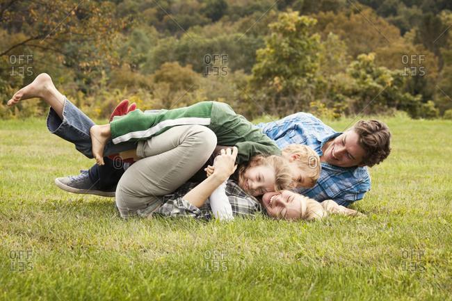 Children wrestling their parents in the grass