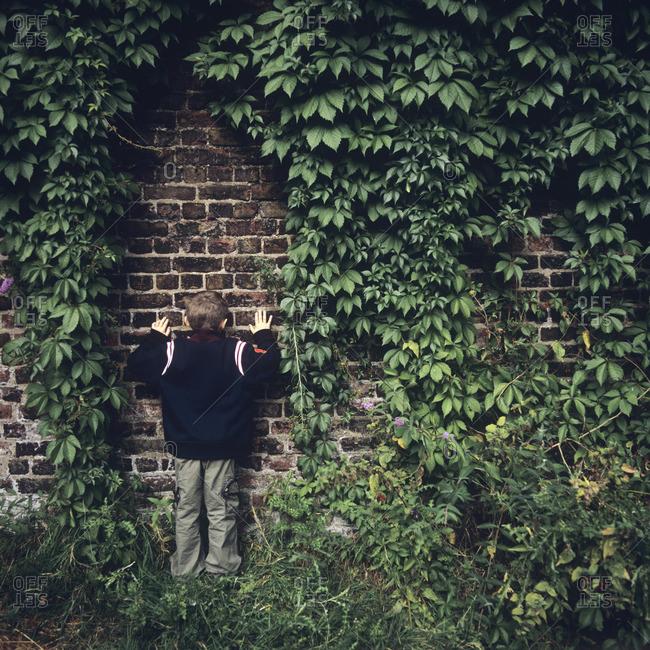 Boy peeping through a brick wall