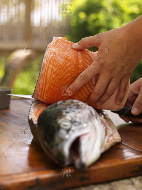 Person filleting a raw fish