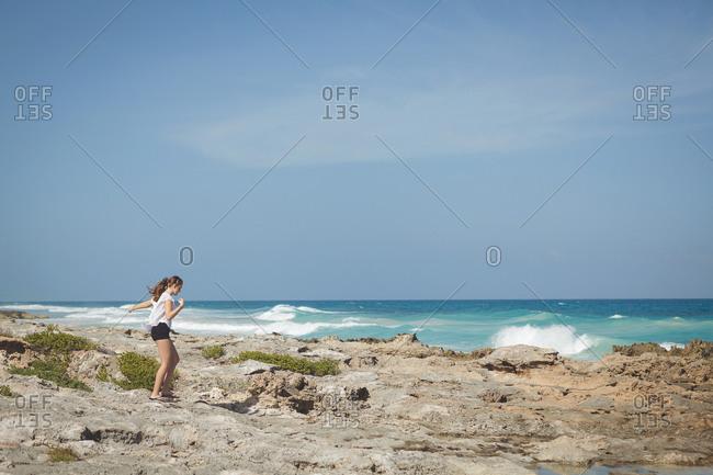 Girl walking along rocky windy coastline