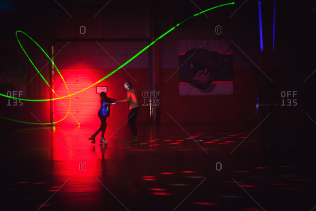Two kids skating in roller rink with light show