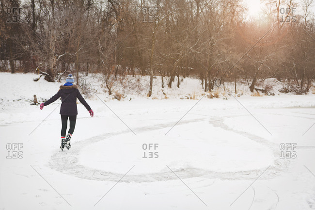 Girl ice skating heart shape onto frozen pond