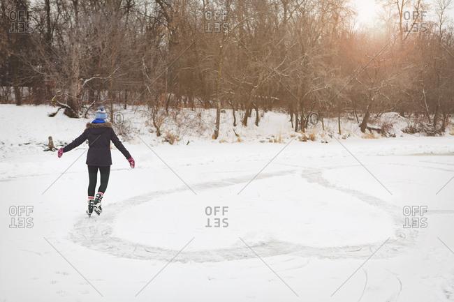 Girl ice skating heart shape onto frozen pond