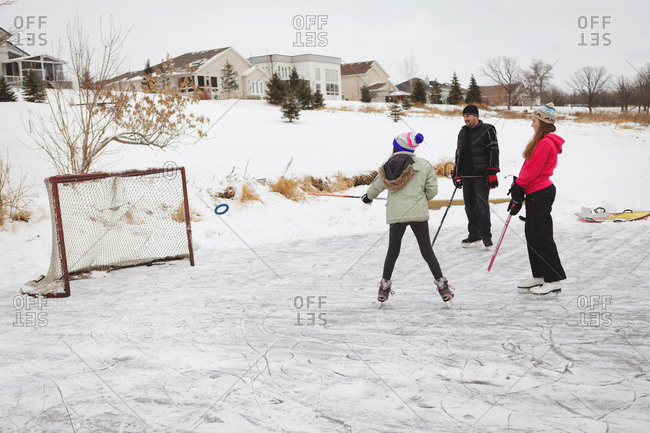 Man and two kids playing hockey in suburbs