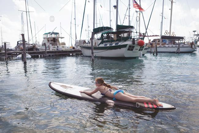 Girl laying on surfboard in marina near boats