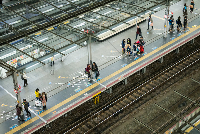 Osaka, Japan - October 30, 2012: Overhead view of people waiting at train platform