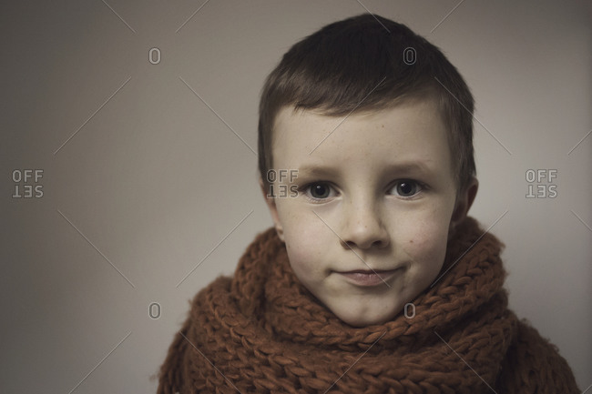 Portrait of a young boy wrapped in knitted scarf