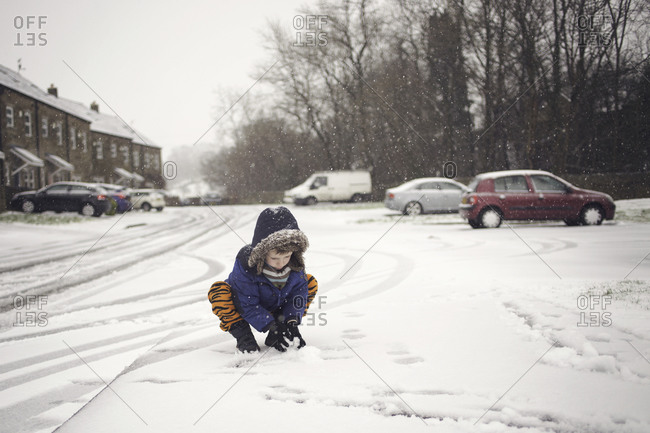 Boy scooping up snow to make a snowball