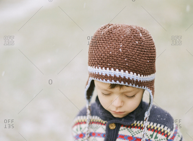 Close-up of sad young boy in knitted winter hat and sweater