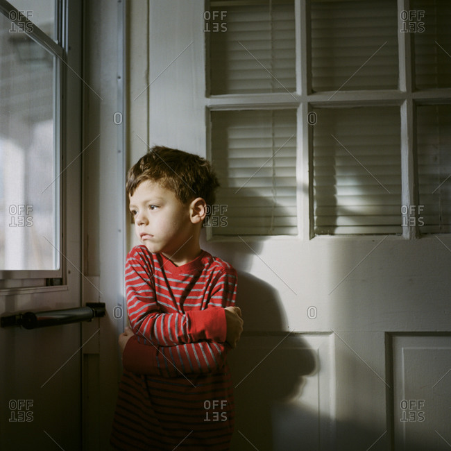 Cold young boy staring out kitchen door