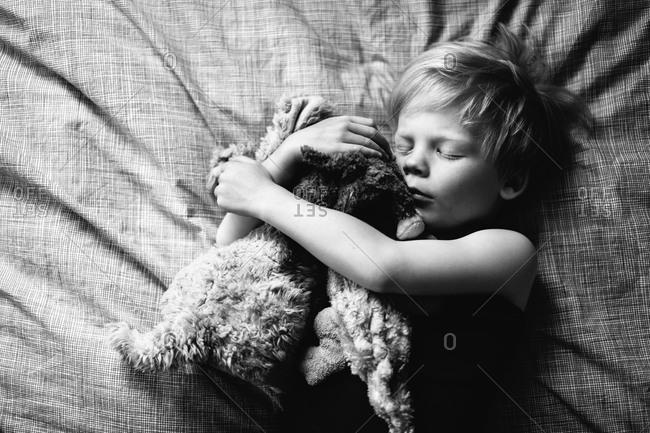 A little boy sleeps with his stuffed animals