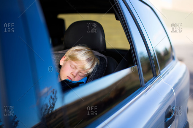 Little boy napping in a car