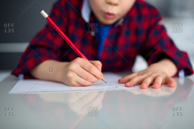 Close up of boy writing on a piece of paper