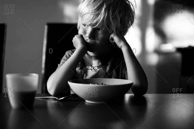 Boy sitting in front of bowl of cereal