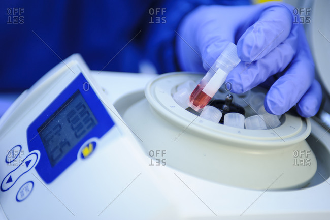 Close up of technician loading samples into a centrifuge in a laboratory