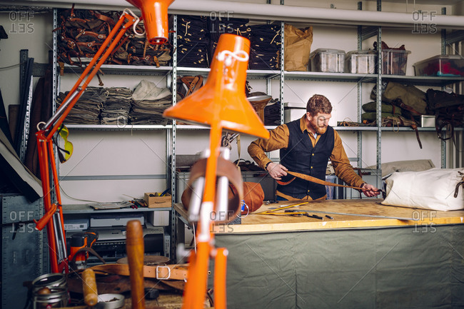 A craftsman unrolls  a leather strap in his workshop