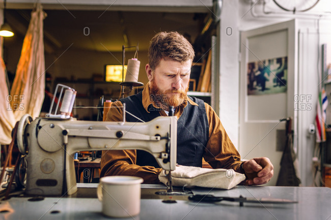 A man examines his handiwork at a sewing machine