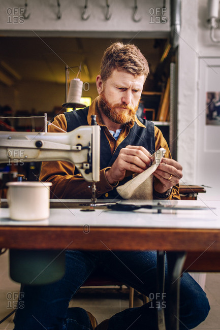 A craftsman examines his handiwork at a sewing machine