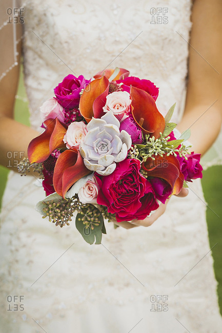 Close up of bride holding modern bridal bouquet with jewel tones