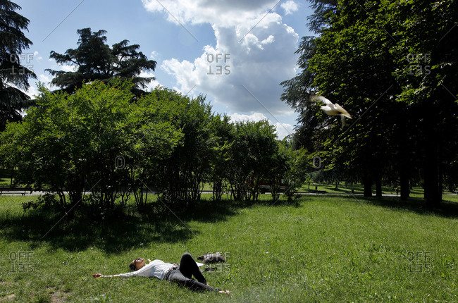 A woman relaxes in the giardini margherita in bologna stock photo
